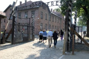 Kazik and Christina go back through the notorious gate he once escaped from - Arbeit Macht Frei - Work Makes you Free - another Nazi lie